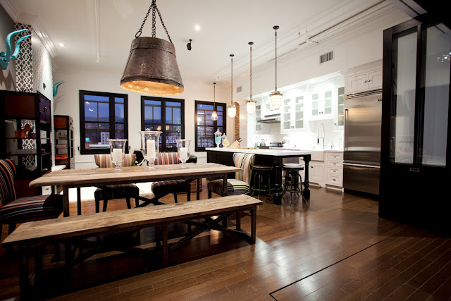 Dining room in Daniel Lowe's Hollywood loft with large bucket inspired pendant light, a rustic industrial wood table and striped chairs and a long bench on one side