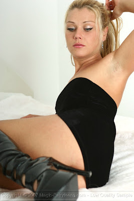 Sexy Blonde Posing in Shiny Boots and Little Black Dress
