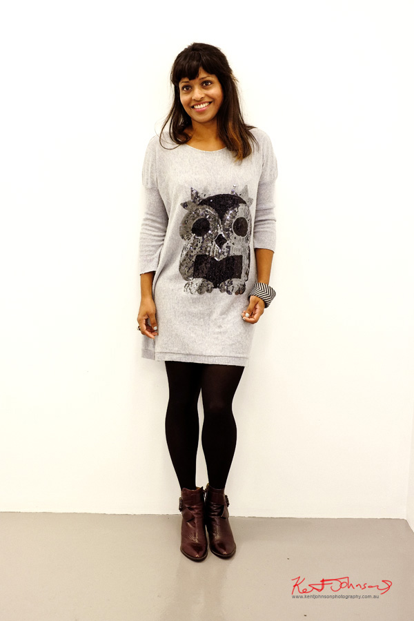 Gray marl knit dress with sequinned owl motif, black tights and brown ankle boots, stripy bangle.