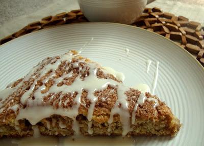 cinnamon roll scone on a white plate with drizzle of vanilla glaze