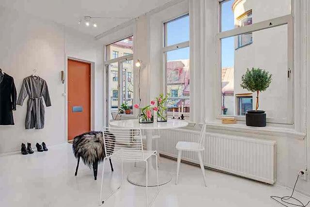Inspirująca biel ścian, mebli i olbrzymie, doświetlające mieszkanie, okna