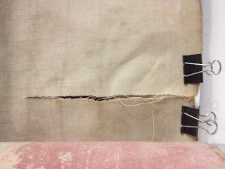 tear in textile to be repaired in the Spicer Art Conservation studio