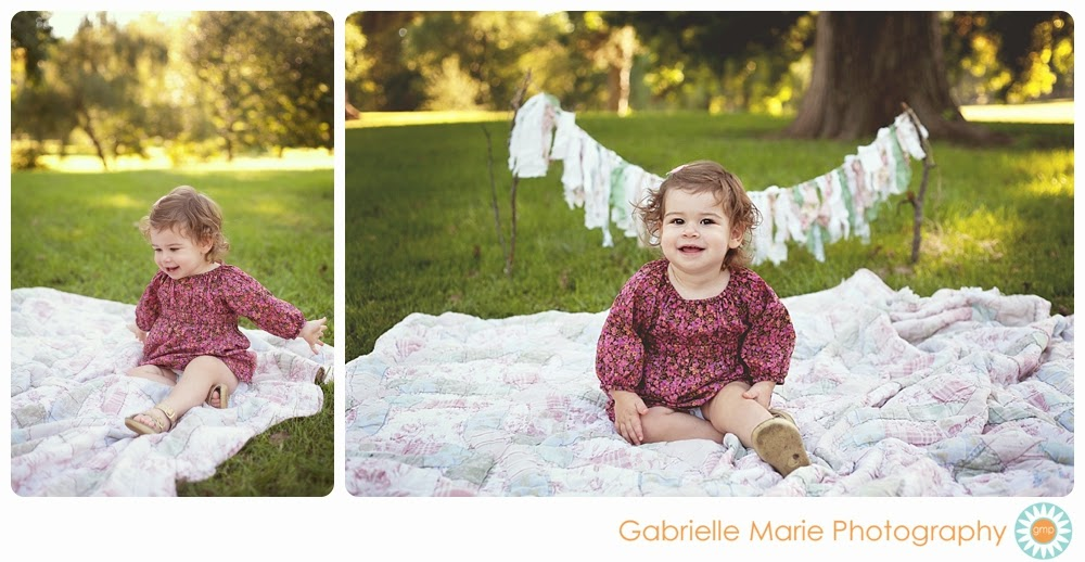 Toddler girl in pink floral print dress sitting on a quilt with a cloth rag banner.