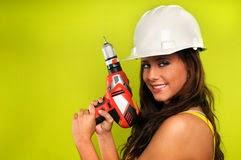 Chica sexy utilizando un gorro de obra y un taladro de bateria