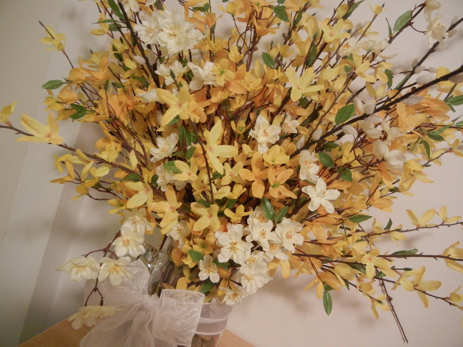 this is my second arrangement so far i used a glass pitcher filled it with medium sized river rocks and made a simple wired ribbon bow - Forsythia Arrangements