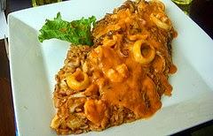 traditional peruvian food tacu tacu covered in mariscos sauce