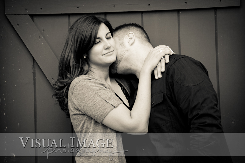 black and white photo of woman with eyes closed while fiance kisses her neck