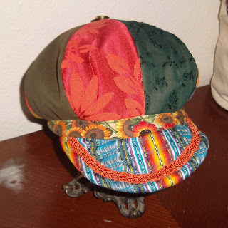 Front view of a eight-paneled crown hat with band around the edge and brim, all constructed from various fabrics in brown, two patterns of orange floral, green lace and blue-multi stripes. Accents include orange braided trim that follows the curve of the brim and a metal sunflower button at the top of the crown where the eight panels come together.