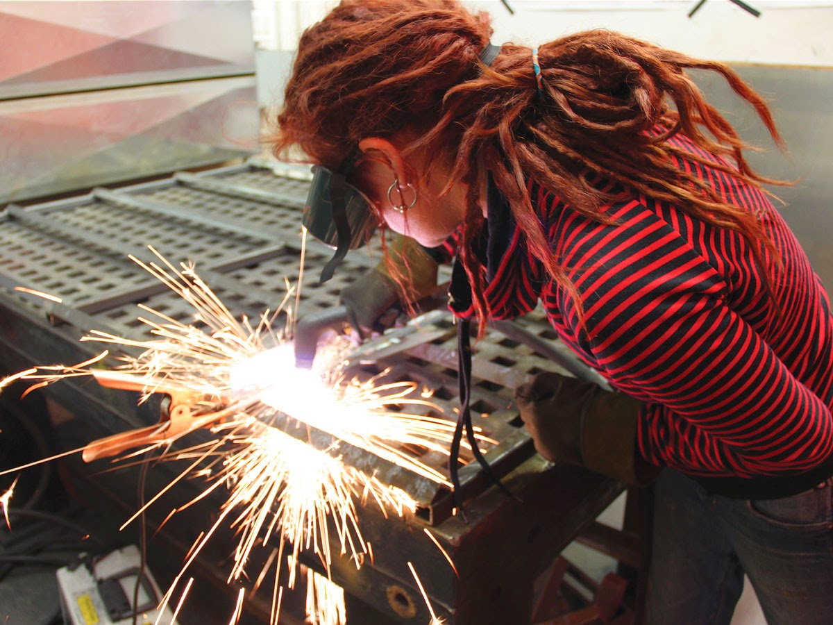 Woman with dredlocks wearing goggles welding