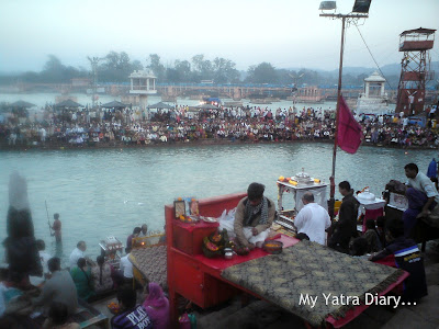 Priests sitting on raised wooden planks at the Har Ki Pauri Ghat, Haridwar