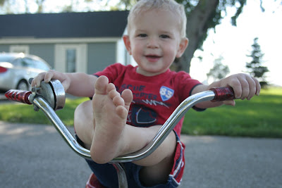 Little boy with Feet up on Tricycle Handlebars: STEM mom