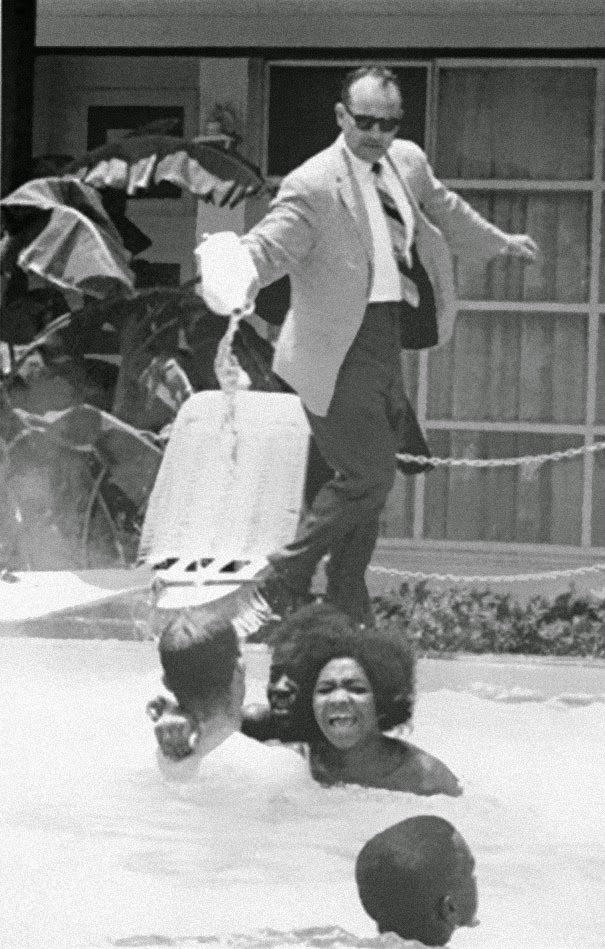 40 Must-See Photos Of The Past - Hotel owner pouring acid in the pool while black people swim in it, ca. 1964