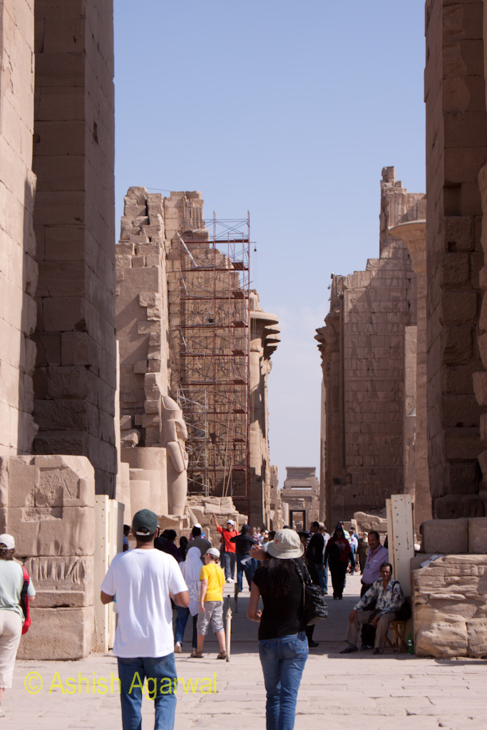 Tourists walking in the path through the middle of the Karnak temple