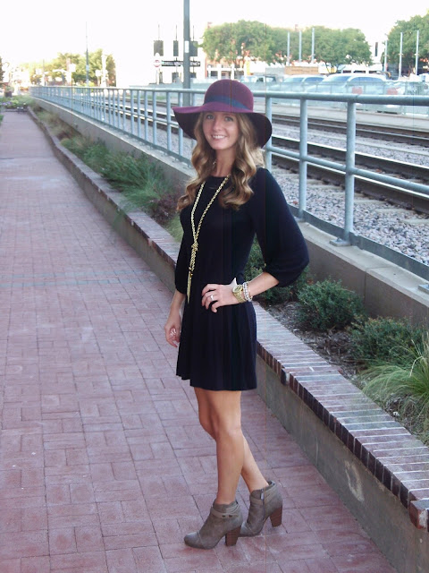 Maroon hat and black shift dress.