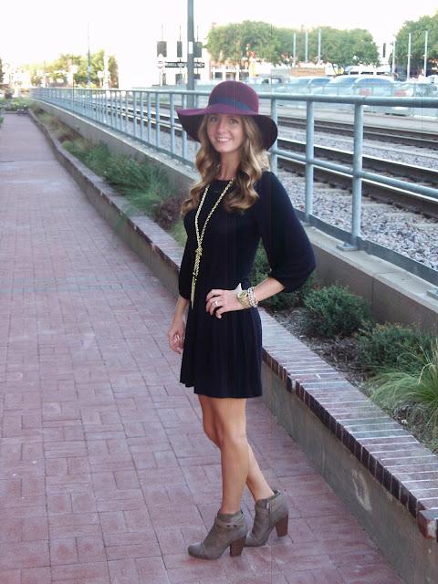 Maroon hat and black shift dress.