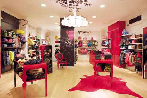 decoracao de interiores lojas:decoração de loja de roupas com o uso de cores fortes como destaque