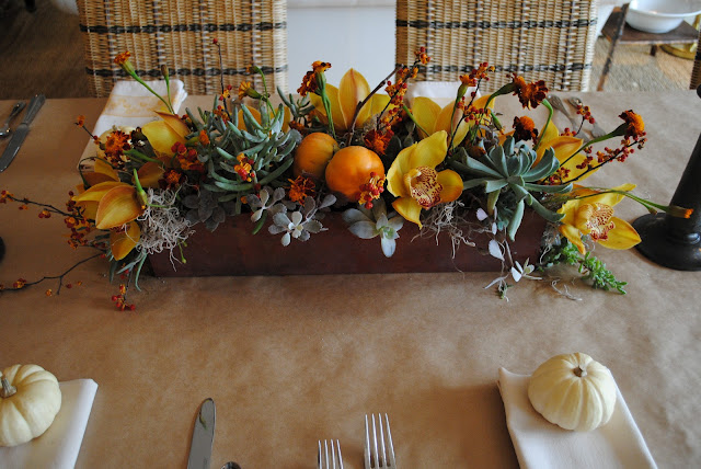 Thanksgiving center piece with copper gutter container.  Orchids, Persimmons, Succulents