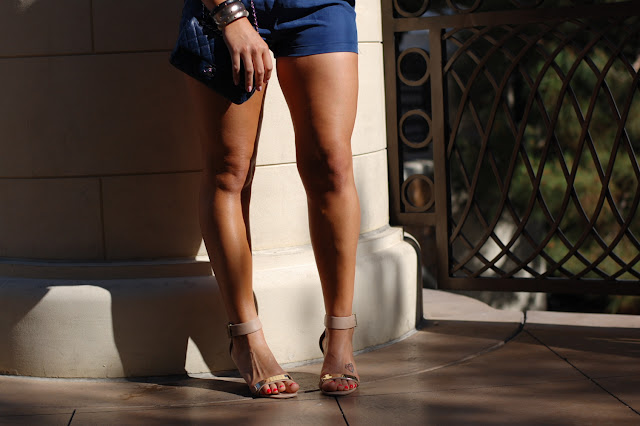 Blue silk romper, Chanel caviar mini handbag, Sam Edelman Serena Sandals and Alexis Bittar bangles.