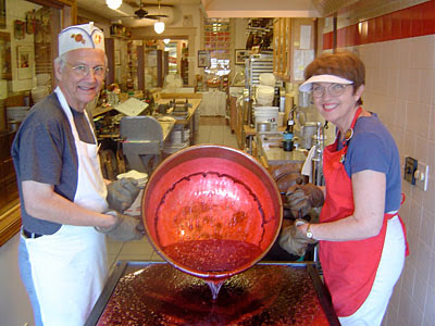 the two owners of schimpffs candy store pouring hot cinnamon syrup out of a big copper kettle to cool to make candy with the store in the background