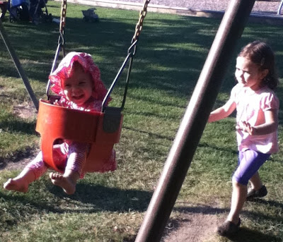 Sisters swinging in the sun.