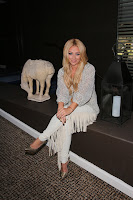 Aubrey O'Day sitting on a bench beside a horse statue