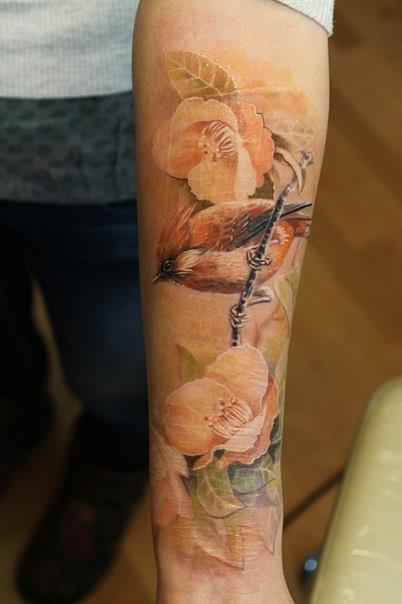 Kolorowy tatuaż ptaka i kwiatów na przedramieniu