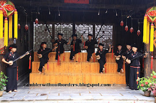 Female Zhuang minority group playing traditional stringed musical instrument ,Yangshuo, Guangxi, China