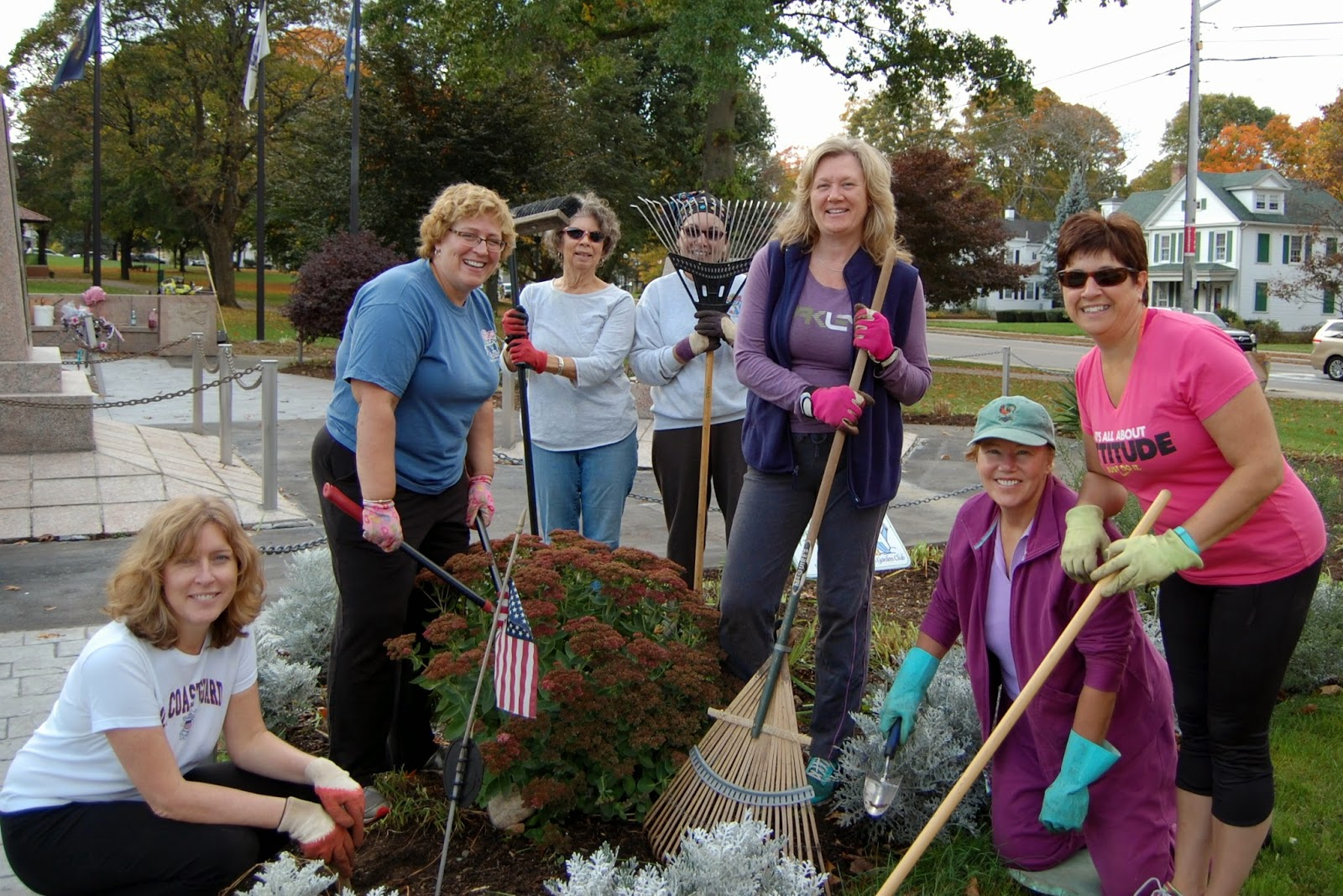 members of the Franklin Garden Club fall cleaning on the flowers around the monuments