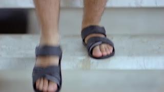 Os pés masculinos do Thiago Lacerda em sandálias Cartago