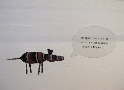 Wall sign in a gallery that reads 'Imagine how small the humans must be to live in such a tiny place'.