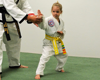 Taekwondo instructor helping a girl with her karate training