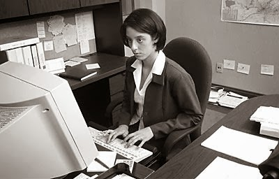 female property manager sitting at a desk typing