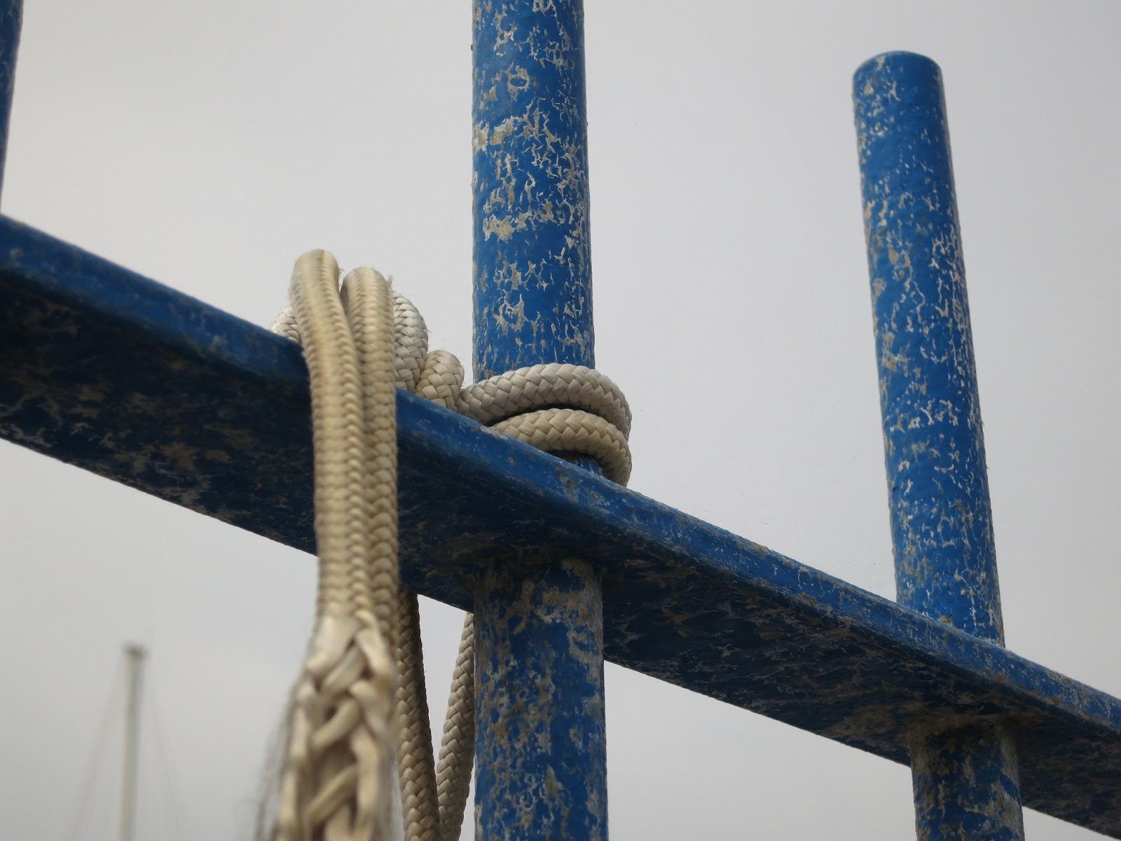 Nylon (?) rope hanging from blue railings with mast in background