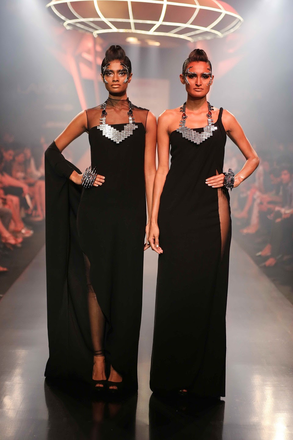 DHL presented the stunning jewellery by Mawi Keivom and the sensational Space Age collection from Gaurav Gupta to close Day Two at Lakmé Fashion Week Summer/Resort 2014. Combing these two haute couture brands of jewellery and garments, the show was a visual treat for the senses. A lit space ship suspended from the ceiling slowly rose to the top at the start of the show, while abstract shapes hung at ramp entrance. To the eerie sounds of a very futuristic symphony, through clouds of smoke, the ultra glam journey into fashionable space started for the audience, as pairs of models in tonal hues but varying designs, decked in outstanding jewellery strutted down the ramp.