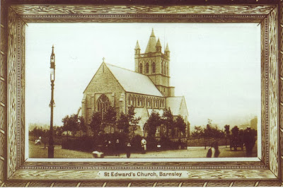 A postcard showing a single aisled church with square tower topped with a little spire.  There are some small new looking trees around the church and a gas lamp in the foreground