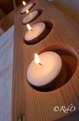 Fyra tända värmeljus i adventsljusstake av trä. foto: Reb Dutius