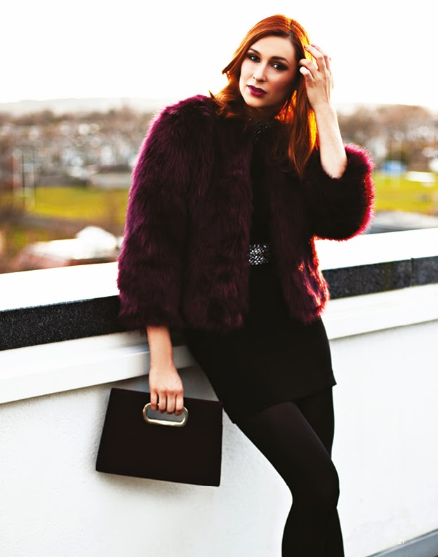 Girl on rooftop wearing a fur coat for a fshion shoot for trend magazine