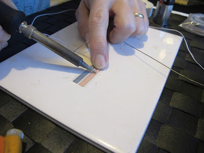 Woman placing the tip of a soldering iron onto a length of wire on a run of copper tape.