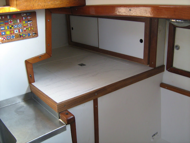 Galley update, installed Corian counters, teak trim and covered cabinet surfaces with white formica