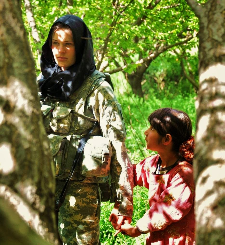 A curious Afghan girl holds the hand of an American soldier. - The 63 Most Powerful Photos Ever Taken That Perfectly Capture The Human Experience