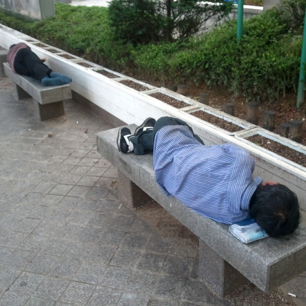 Dos coreanos durmiendo en los bancos de una calle de Seúl