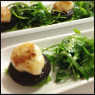Scallops with black pudding, pea purée & rocket salad