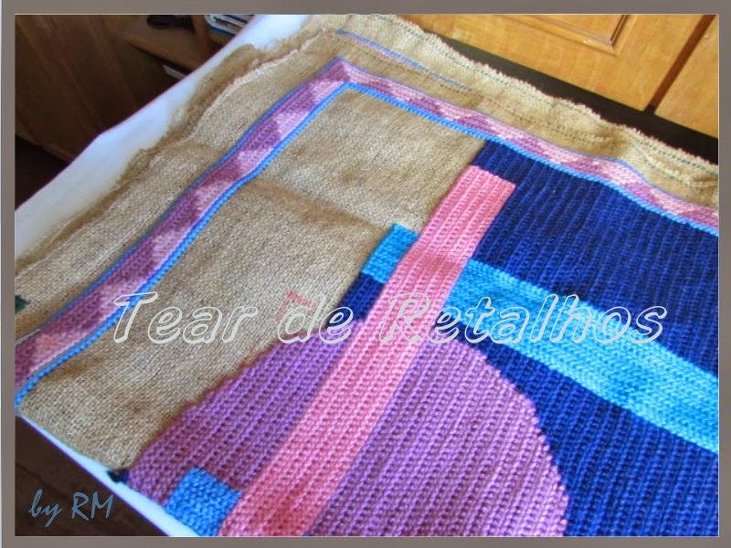 Execução de bordado em tela, preenchendo-se os espaços da tela com pontos de tapeçaria.