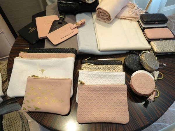 Faux leather embossed clutches, pouches, and luggage tags in blush, cream, and black