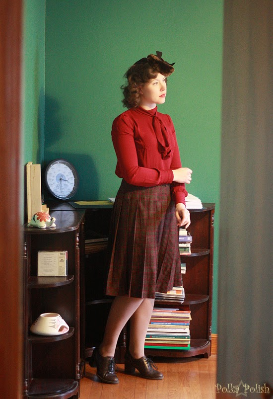 1940s collegiate inspired outfit with beaver tilt hat, plaid skirt, laced shoes, and pussy-bow blouse