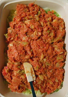 Spreading Tomato Sauce Over Meat and Cabbage