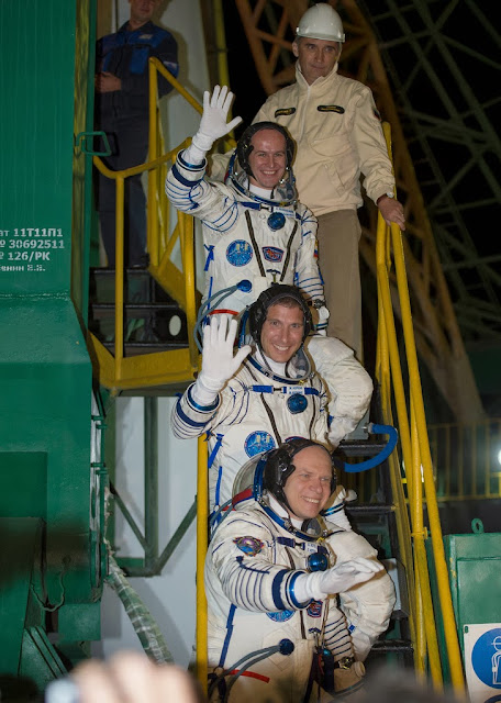Expedition 37 Russian Flight Engineer Sergey Ryazanskiy, top, NASA Flight Engineer Michael Hopkins, Soyuz Commander Oleg Kotov, bottom, wave farewell from the base of the Soyuz rocket at the Baikonur Cosmodrome in Baikonur, Kazakhstan, Thursday, Sept. 26, 2013. Their Soyuz TMA-10M rocket is scheduled to launch at 2:58 a.m. local time. Photo Credit: (NASA/Carla Cioffi)