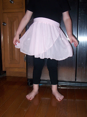 little girl in black leggings and white skirt