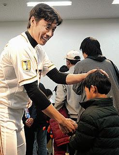 ファンと笑顔で握手をする鈴木尚
