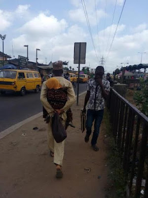 Father Backs His Child Walking In Lagos